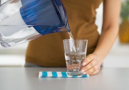 Nahaufnahme auf Hausfrau gießt Wasser in Glas von Wasser-Filter Krug Standard-Bild - 21341897