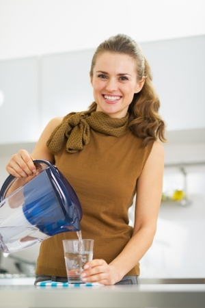 Lachende jonge huisvrouw gieten van water in glas uit het water filter werper Stockfoto