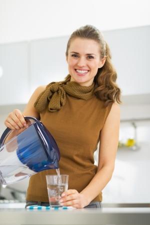 agua purificada: Sonriente joven ama de casa vertiendo agua en vidrio de la jarra del filtro de agua