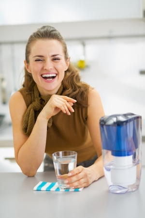 Happy young housewife drinking water from water filter pitcher in kitchen