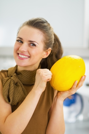 ripeness: Happy young housewife checking ripeness of melon