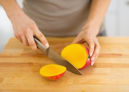 Closeup on woman cutting mango photo