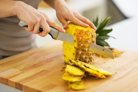 Closeup on woman cutting pineapple Imagens
