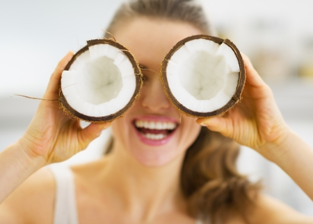 Smiling young woman holding two pieces of coconut in front of eyes