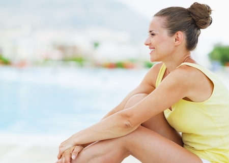 Happy young woman sitting on sunbed photo