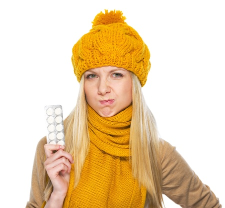Frustrated young woman in hat and scarf with pack of pills Stock Photo - 21354875