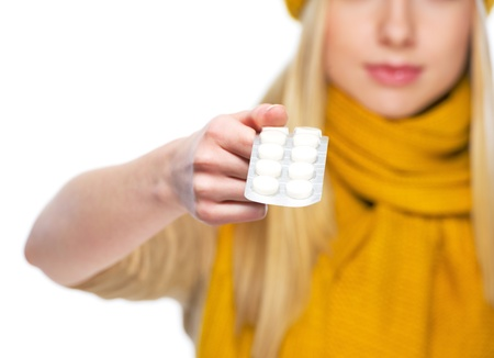 Closeup on pack of pills in hand of young woman in hat and scarf photo