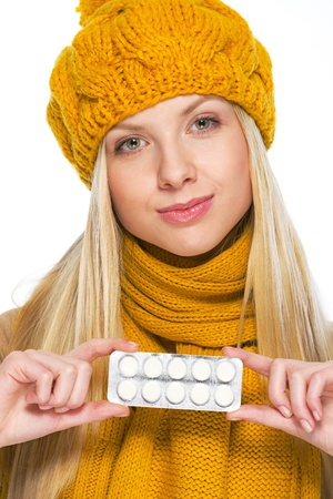 Young woman in hat and scarf showing pack of pills Stock Photo - 21354880
