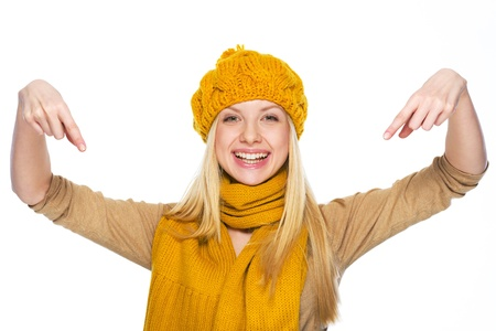 Smiling young woman in hat and scarf pointing down on copy space Stock Photo - 21354893