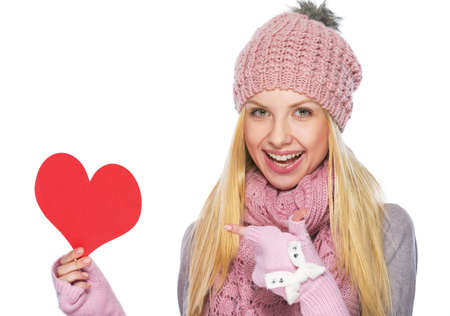 Happy teenager girl in winter hat and scarf pointing on heart shaped postcard photo