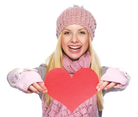 Smiling teenager girl in winter hat and scarf showing heart shaped postcard photo
