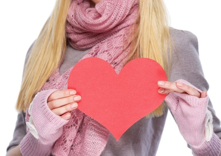 Closeup on heart shaped postcard in hand of teenager girl in winter gloves and scarf photo