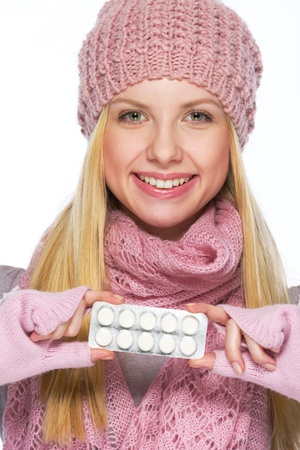 Portrait of smiling teenager girl in winter hat and scarf showing pills pack Stock Photo - 21354856