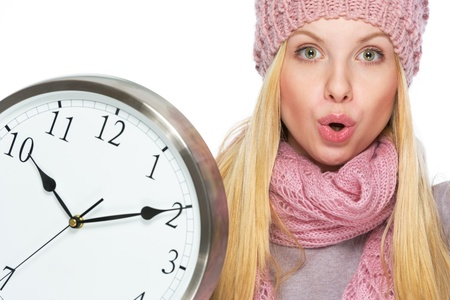 Portrait of surprised teenager girl in winter hat and scarf with clock photo