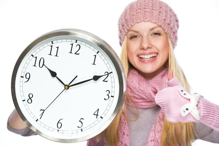 Happy teenager girl in winter hat and scarf showing clock and thumbs up photo
