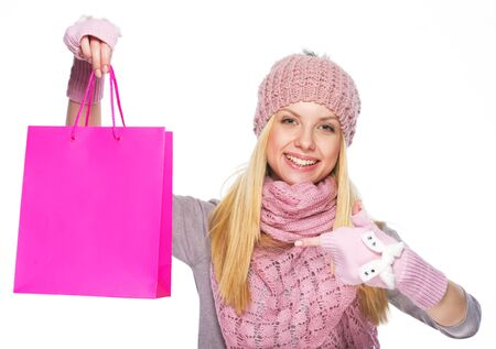 Happy teenager girl in winter hat and scarf pointing on shopping bag Stock Photo - 21354814