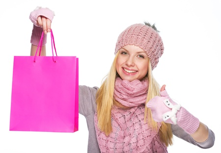 Smiling teenager girl in winter hat and scarf showing shopping bag and thumbs up photo
