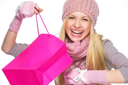 Portrait of smiling teenager girl in winter hat and scarf opening shopping bag Stock Photo - 21354819