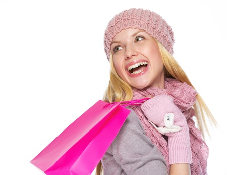 Smiling teenager girl in winter hat and scarf with shopping bag looking on copy space Stock Photo - 21354823