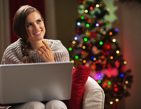 Smiling young woman with laptop near christmas tree looking on copy space Stock Photo - 21568001