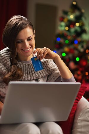 Smiling young woman with laptop and credit card near christmas tree Stock Photo - 21568003