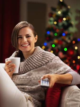 Happy young woman with cup of hot beverage near christmas tree watching tv Stock Photo - 21568027