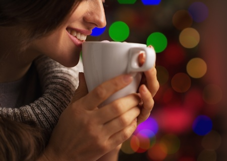 Closeup on smiling young woman with cup of hot chocolate with marshmallow in front of christmas lights Stock Photo - 21568034