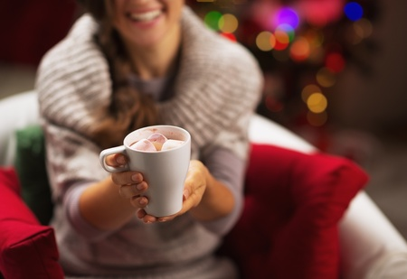 Closeup on cup of hot chocolate with marshmallow in hand of smiling young woman Stock Photo - 21568055