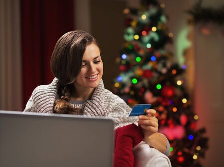 Happy young woman near christmas tree making online shopping Stock Photo - 21568065