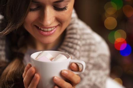Happy young woman holding cup of hot chocolate with marshmallow Stock Photo - 21568075