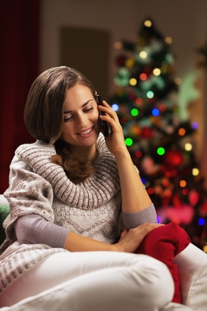 Young woman talking cell phone near christmas tree Stock Photo - 21568081