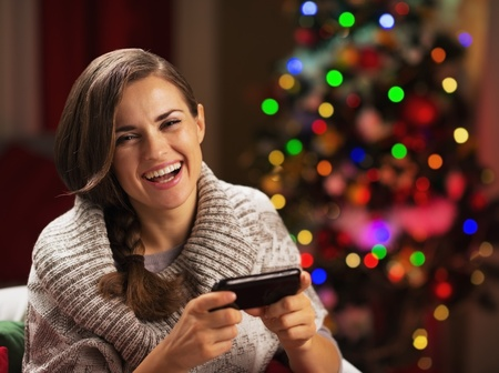 Happy young woman writing sms near christmas tree photo