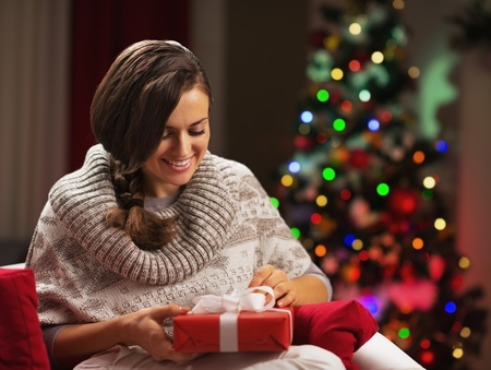 Happy young woman near christmas tree with present box Stock Photo - 21568097