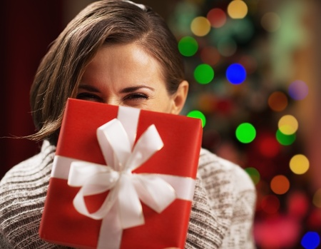 blissful: Happy young woman holding christmas present box in front of face Stock Photo