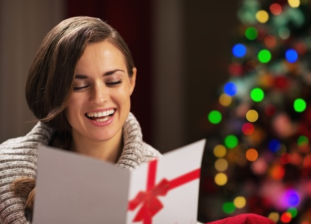 Smiling young woman reading christmas postcard in front of christmas lights Stock Photo - 21568124