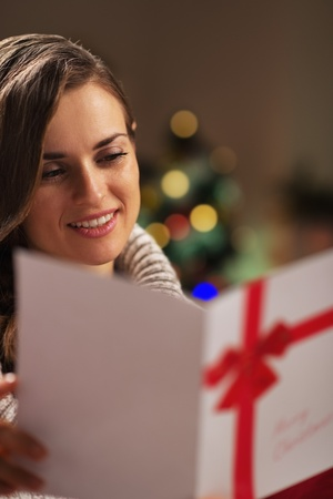 Portrait of happy young woman reading christmas postcard Stock Photo - 21568126