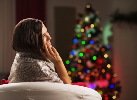 Happy young woman talking mobile phone in front of christmas tree Stock Photo - 21568133