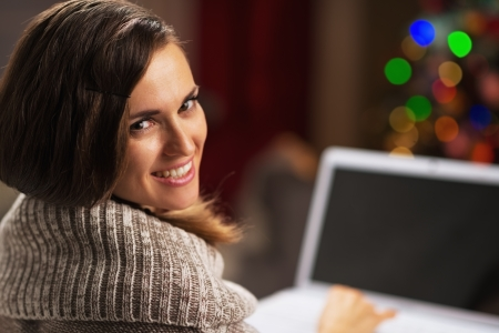 Happy young woman with laptop in front of christmas tree Stock Photo - 21568172