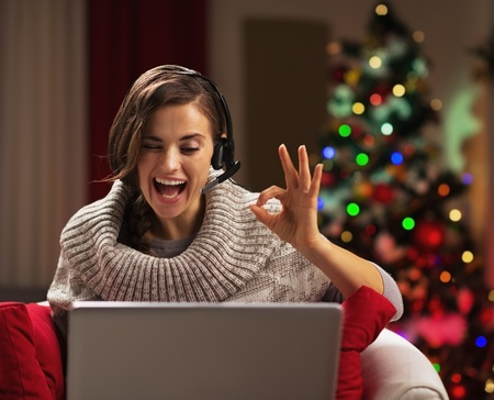 Smiling young woman showing ok gesture while having video chat in front of christmas tree Stock Photo - 21568179
