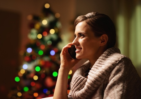 Happy young woman talking cell phone in front of christmas tree Stock Photo - 21568194