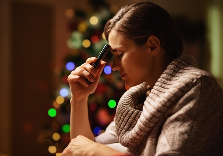 disquieted: Concerned young woman with mobile phone in front of christmas tree