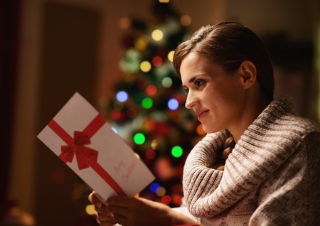 Happy young woman reading postcard in front of christmas tree photo