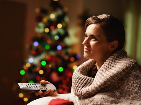Happy young woman watching tv in front of christmas tree Stock Photo