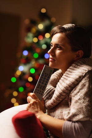 tv remote: Thoughtful young woman with tv remote control in front of christmas tree Stock Photo