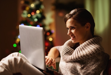 christmas eve: Happy young woman working on laptop in front of christmas tree Stock Photo