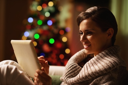 Happy young woman using tablet pc in front of christmas tree photo