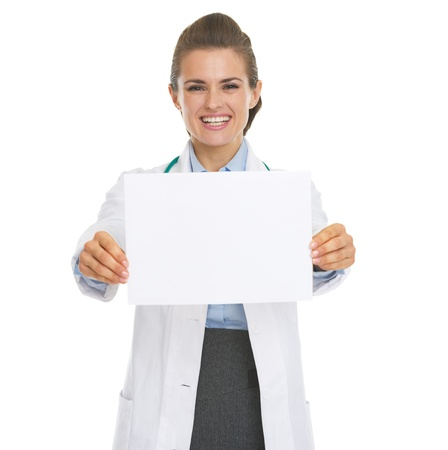 Smiling doctor woman showing blank paper sheet photo