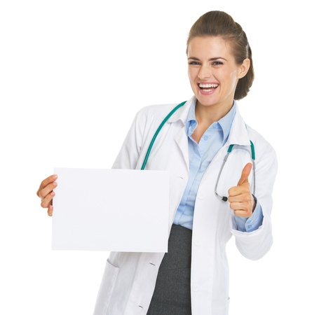 Happy doctor woman showing blank paper sheet and thumbs up photo