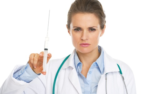 Portrait of serious doctor woman holding syringe photo