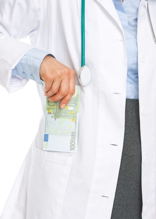 doctor putting money: Closeup on doctor woman putting stack of euros in pocket